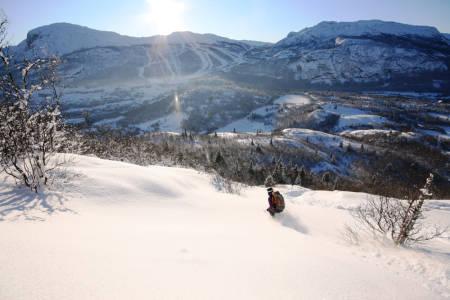 PÅ TUR: Ida Siem kjører ned fra Rustehaugnosi med skisenteret i bakgrunnen. Foto: Jørgen Aamot
