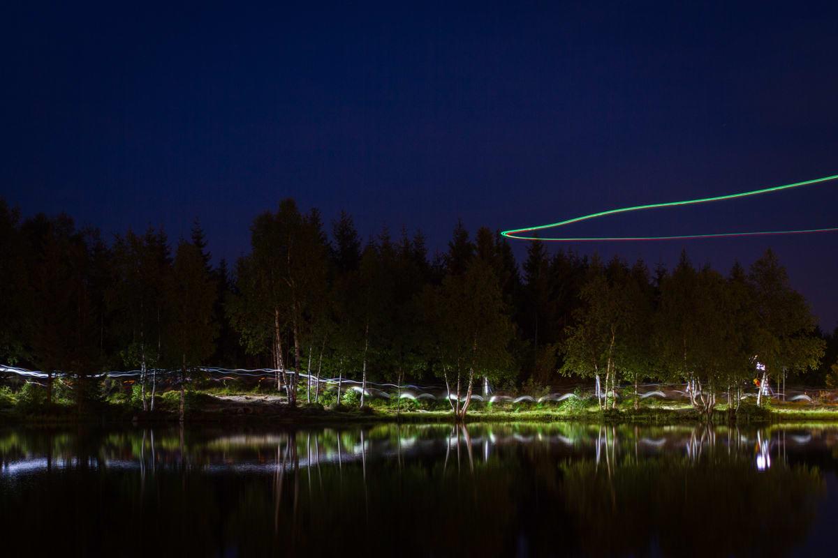 LYS I MØRKET: Hodelyktene danner kunstneriske striper langs vannkanten. Fra luften filmer en drone løperne.