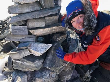 Astrid Furholt ved Roald Amundsens varde på Bettyfjellet, hvor han satte igjen en kanne parafin, fyrstikker og en hermetikkboks. Foto: Jan Sverre Sivertsen