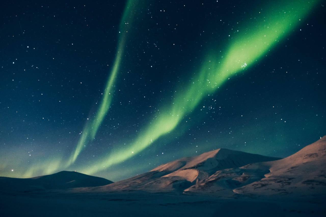 NATURLIG LYS: Dagnordlyset danser over tause fjell i Adventdalen. Foto Dagmara Wojtanowicz