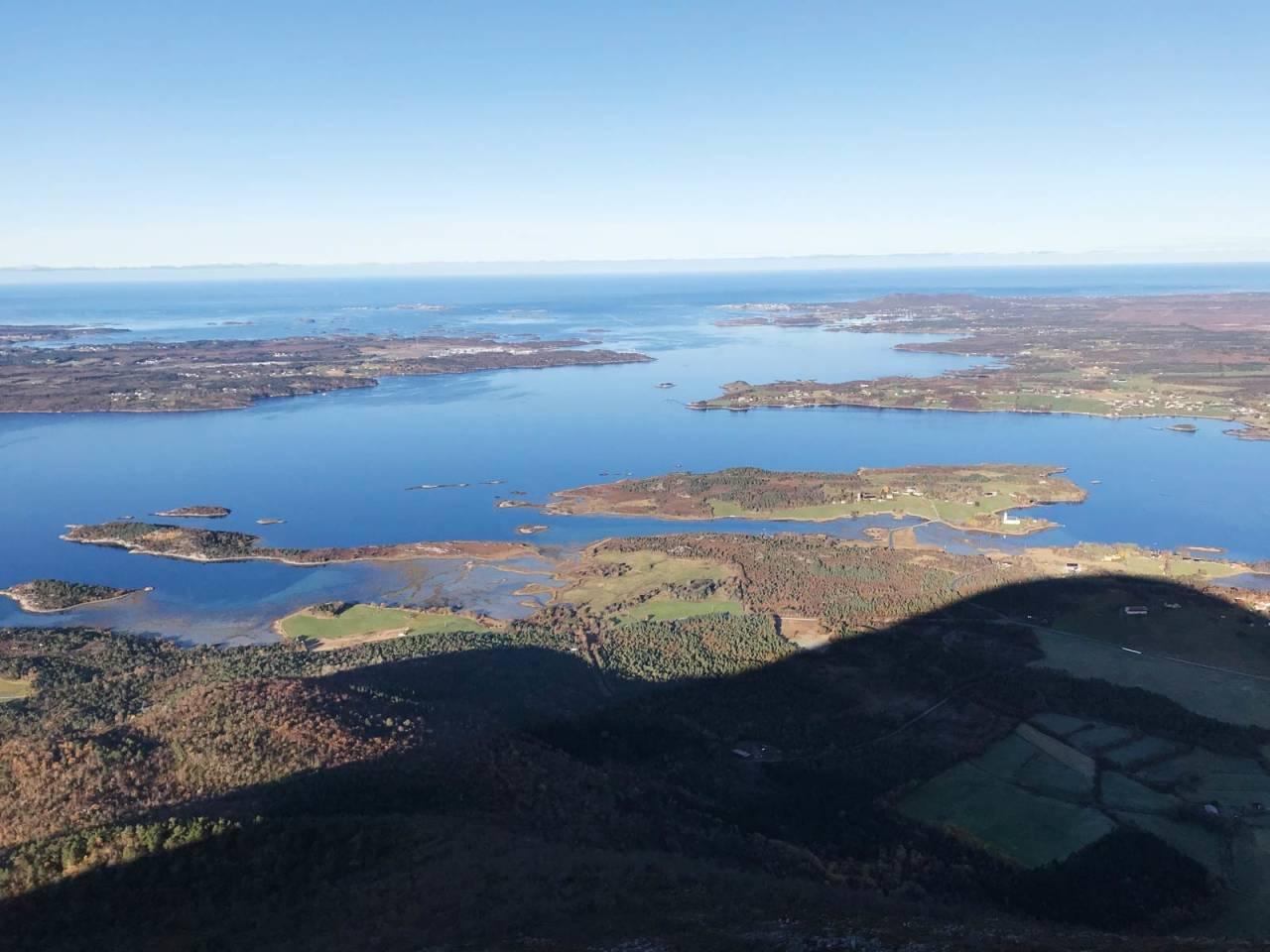 JENDEMSFJELLET: Bildet viser skyggen av østryggen og utsikt fra toppen mot romsdalskysten med Vågsøya, Gossen, Bud og Hustadvika. Foto: Iver Gjelstenli