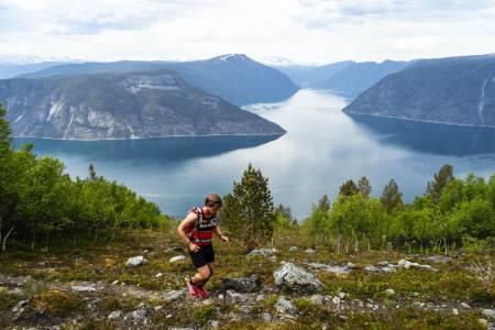 Henrik på vei opp mot Bermålsnosi med Lustrafjorden bak. Foto: Sondre Kvambekk/500fjell.no