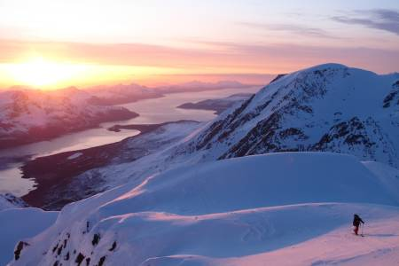 TROMS: Jiehkkevárri (også kjent som Jiekkevarri eller Jiekkevarre) er det høyeste fjellet i Troms på 1834 moh (Tromsø kommune). Toppen er kjennetegnet av en stor brekuppel som i tillegg til fjellets beliggenhet gjør toppen fysisk, men ikke teknisk, krevende å bestige. Fjellet er det høyeste og mest dominerende i Lyngsalpene, og kan sees på lang avstand. Mange mener at Jiehkkevarri på langs er den flotteste høyfjellstravers i Norge som du kan gjøre på en dag og blir av mange omtalt som «Norges Haute Route». Lengden er ca 30 km og antall høydemeter inntil 2400. Det er flere gode ruter opp, mens vi valgte å gå samme vei opp og ned via Holmbukttind. Jiehkkevarri utmerker seg ved at store deler av turen gir en utsikt en ikke er vant til. Fjell og hav om hverandre og i vårt tilfelle som startet 18 på kvelden, lystet av midnattsolen. Vi trasket totalt 12 timer på natten, var trøtte som fy da vi var ferdige, men høye så det holdt på naturopplevelsen! Det ble ikke mindre artig at vi gikk denne turen natt til 17. mai og fikk med oss feiringen i Tromsø by etter et par timer på øyet. Anbefaler alle som ikke har vært i Troms på vinterstid å reise hit – et eldorado for topptur! Vi gikk turen på randonee, men jeg har hørt mange har gått traversen på fjellski.