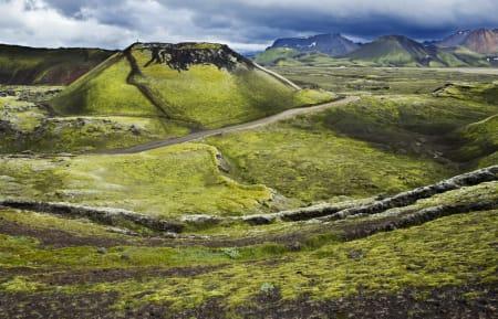 Vulkansk krater med et lite menneske på toppen. Man føler seg fort liten i islandsk natur!