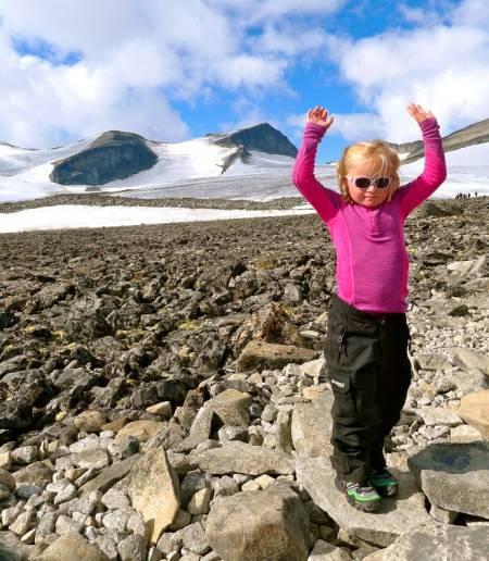 OPP MED DOWN: Marikken, 6 år gammel, strekker hendene i været etter å ha nådd Galdhøpiggen. Foto: Eivind Eidslott