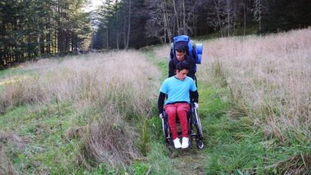 Samarbeid: Yeison Reyes Santos (Columbia) som hjelper Melvin Cornejo Gomez (El Salvador) I rullestolen mangler en fot etter at han som sjuåring tråkka på en landmine i et grenseområde mellom Geriljaen og regjeringssoldater i Colombia. Yeison får oppfølning på Røde Kors Haugland rehabiliteringssenter og er blant de mest aktive UWC-elevene. Foto: Hilde Genberg