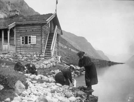 Kristine Bonnevie og Alette Falch (Schreiner) vasker klær ved Gjendebu sommeren 1896. De har vært på fottur sammen med Vilhelm Bjerknes (sittende til venstre) og Alfred Bryn (fotograf). Tilhører MUV, Universitetet i Oslo.