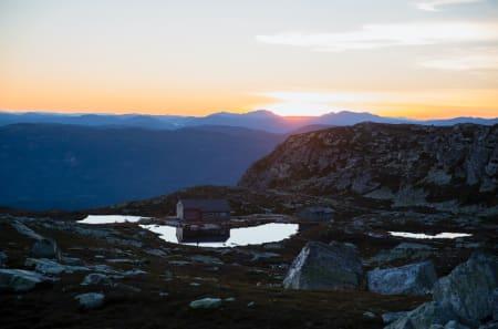 LYSET SLUKKAST: Sola sender sine siste stråler over Sigridsbu. Frå teltet mitt var det vanskeleg å spore liv der nede i hytta, og eg måtte innsjå at eg, Eik og min livlege fantasi kom til å vere åleine på fjellet gjennom natta.