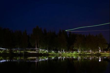 UTFORSK NATTELIVET: Bruk stativ og lang lukkertid nattestid. Her et bilde fra nattorienteringsstafetten Night Hawk ved Øvresetertjern. Over vannet sirkler en drone som filmer løperne. Bildedata: Lukkertid: 25s. Blenderåpning: f/11. Lysfølsomhet: ISO 100. Brennvidde: 64mm. Foto: Snorre Veggan