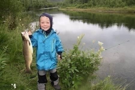 TØFFING: Jon Andreas (5) fikk denne sværingen av en fisk på fisketur i Dividalen. Se video i saken. Foto: Familien Rønneberg