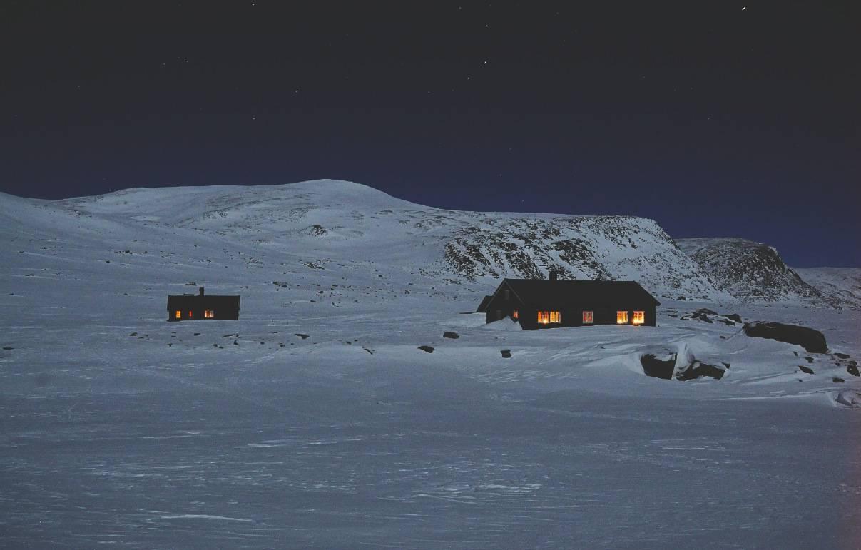 LYS I MØRKET: Reinheim består av en stor og en mindre hytte og har til sammen 36 sengeplasser. Turen inn til Reinheim fra Kongsvold er 17 kilometer. Fra Reinheim er det også kvistet til Åmotdalshytta, en annen selvbetjent DNT-hytte. Foto: André Spica