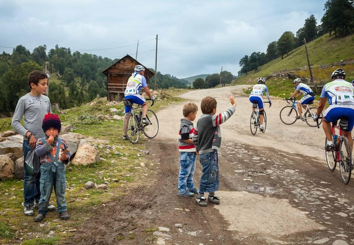 PÅ VEIEN: Syklistene hilser på en georgiske barn i en landsby ved Goderzi-passet på vei til svartehavsbyen Batumi. Foto: Hans Aage