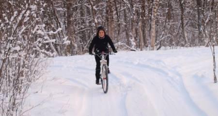 Klar for ville veier: Snø og minusgrader i Tromsø minner lite om det Sigrid Mogård kommer til å oppleve i Afrika. – Men det er fin måte å øve på litt teknisk sykling, sier hun. Foto: Privat